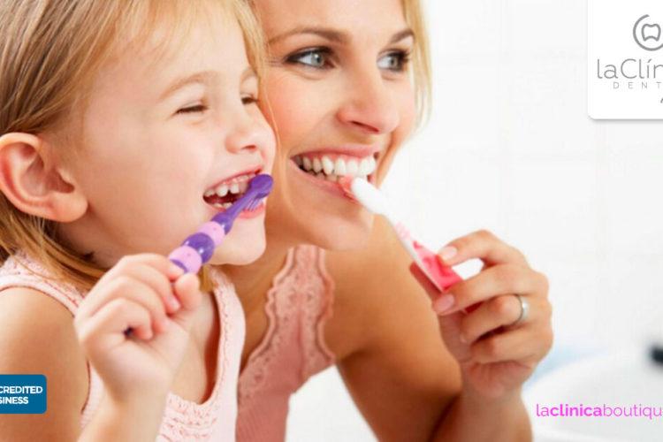 Enseñar a los niños a lavar sus dientes es parte de su salud dental